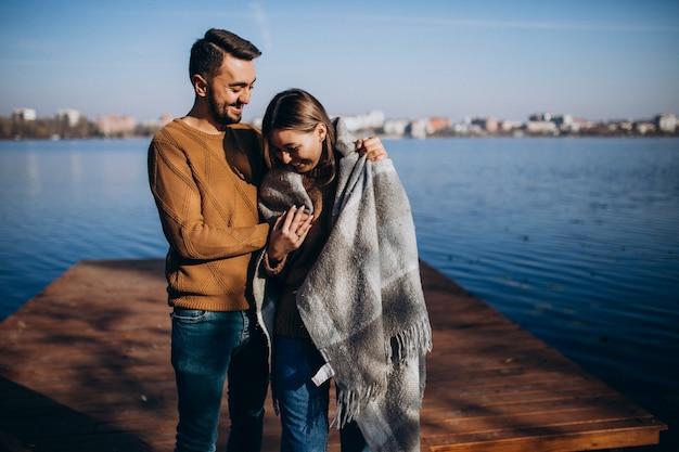 Casal feliz com cobertor pelo rio