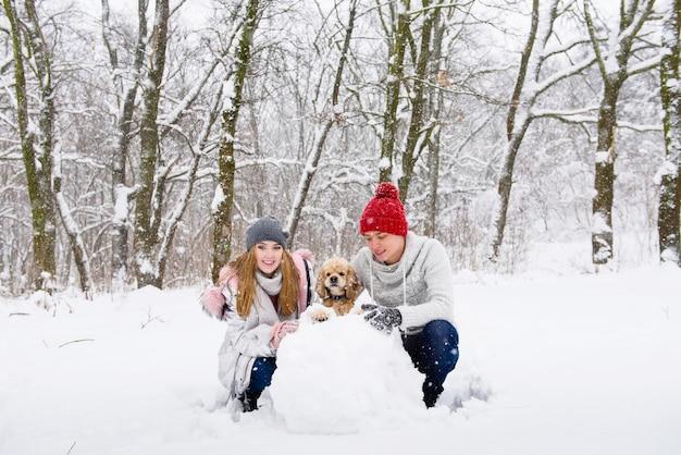 Casal feliz com cocker spaniel fazendo boneco de neve