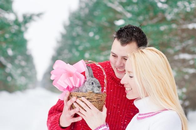 Casal feliz com coelho ao ar livre