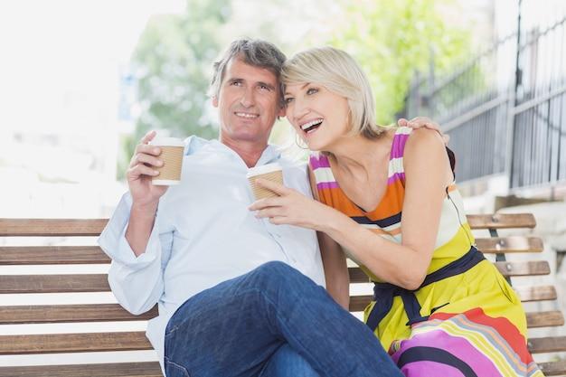 Casal feliz com copos de café no parque