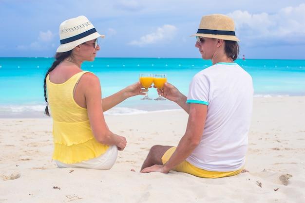 Casal feliz com copos de suco de laranja na praia tropical