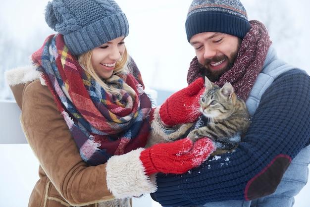 Casal feliz com gato em dia de inverno