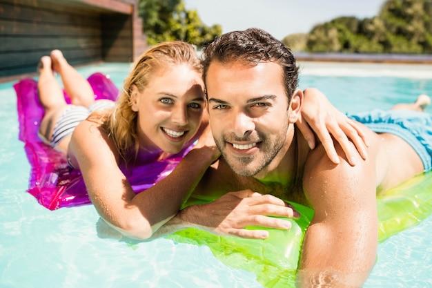 Casal feliz com lilos na piscina em um dia ensolarado