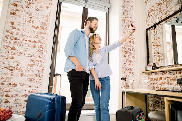 Casal feliz com malas se divertindo no quarto de hotel e tirando foto de selfie no smartphone