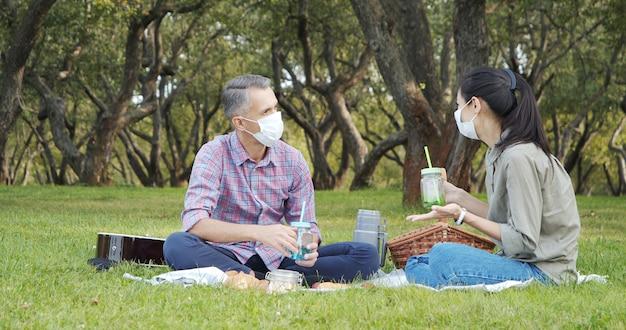 Casal feliz com máscaras médicas protetoras, conversando enquanto está sentado na grama do parque.