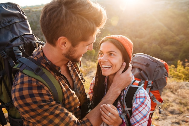 Casal feliz com mochilas nas montanhas