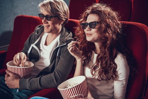 Casal feliz com óculos 3d come pipoca