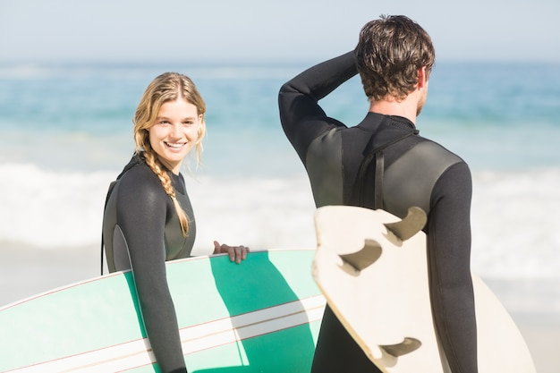Casal feliz com prancha de pé na praia