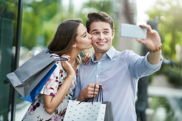 Casal feliz com sacolas de compras depois de fazer compras na cidade, sorrindo e se abraçando.