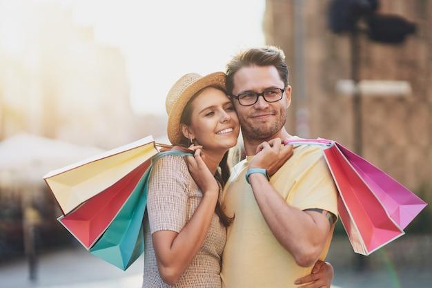 Casal feliz com sacolas de compras na cidade