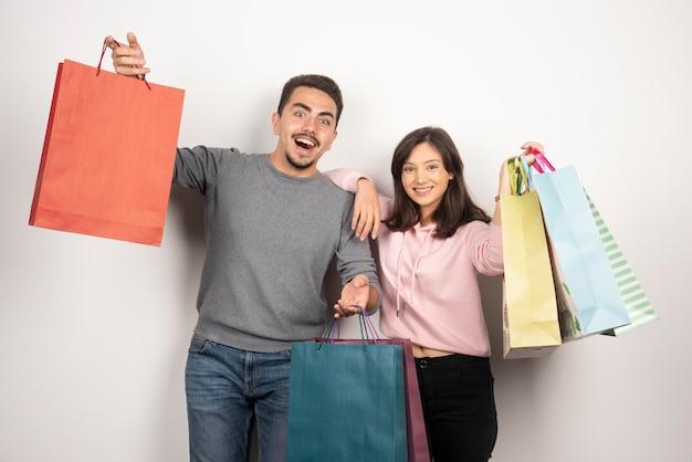 Casal feliz com sacolas de compras, posando em branco.