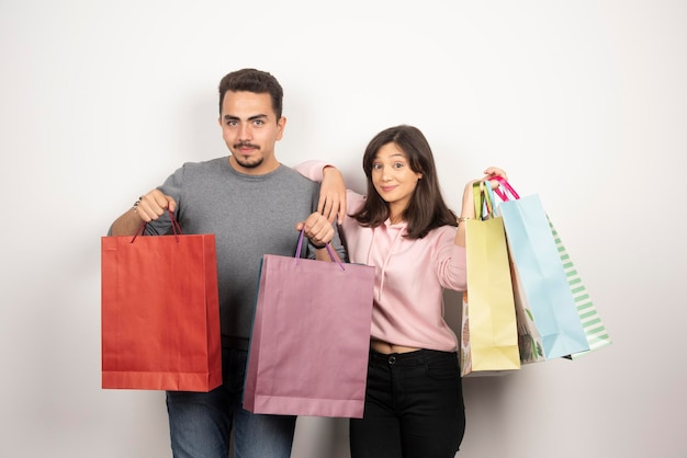 Casal feliz com sacolas de compras posando.