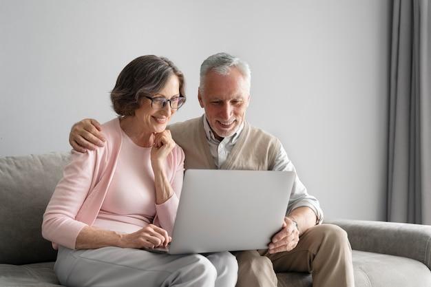 Casal feliz com tiro médio com laptop