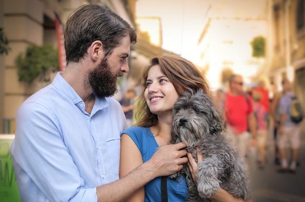 Casal feliz com um cachorro andando na cidade