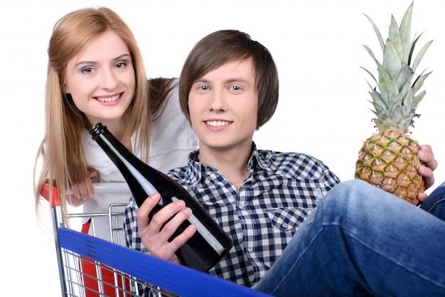 Casal feliz com um carrinho de compras.
