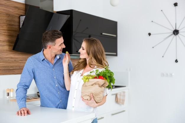 Casal feliz com um pacote de produtos em pé e flertando na cozinha em casa
