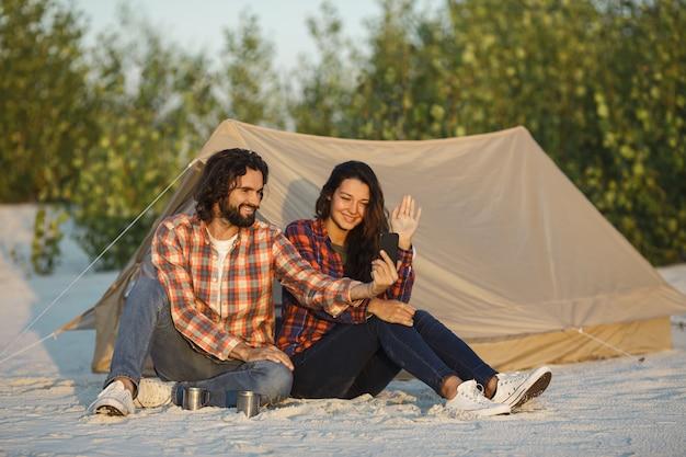 Casal feliz com um smartphone no acampamento perto da barraca ao ar livre
