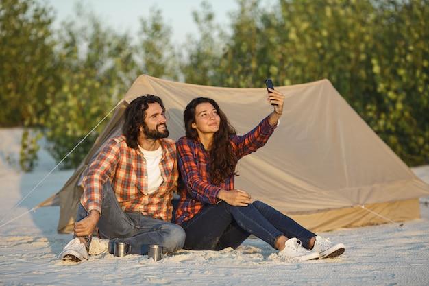 Casal feliz com um smartphone no acampamento perto da tenda ao ar livre
