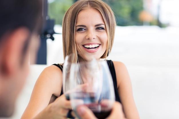 Casal feliz comemorando algo em restaurante com vinho tinto