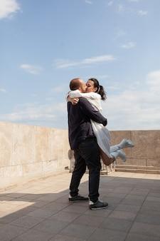 Casal feliz comemorando aniversário de relacionamento no telhado do prédio