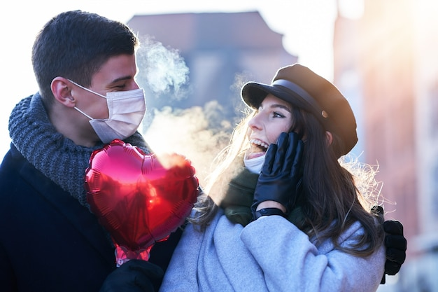 Casal feliz comemorando o dia dos namorados com máscaras durante a pandemia covid-19 na cidade