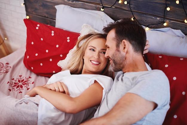 Casal feliz comemorando o natal na cama