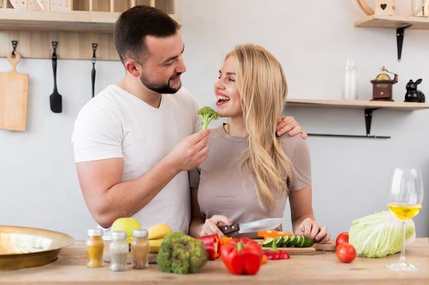 Casal feliz comendo brócolis