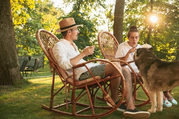 Casal feliz comendo e bebendo cerveja em um jantar de churrasco na hora do pôr do sol