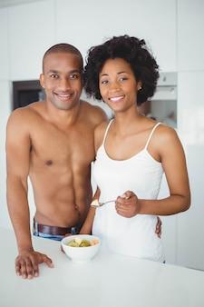 Casal feliz comendo frutas juntos na cozinha em casa