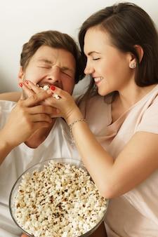 Casal feliz comendo pipoca e assistindo filme em casa