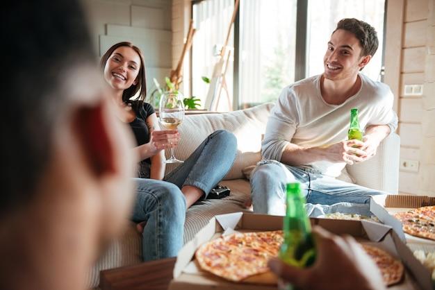 Casal feliz comendo pizza, bebendo cerveja e vinho com os amigos