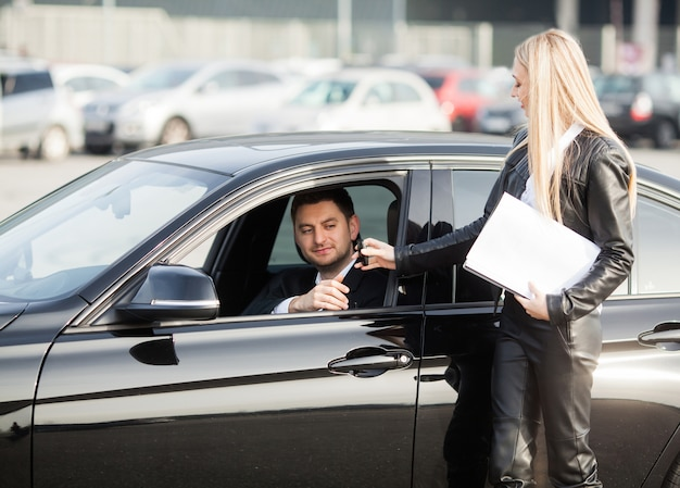 Casal feliz compra novo carro preto moderno