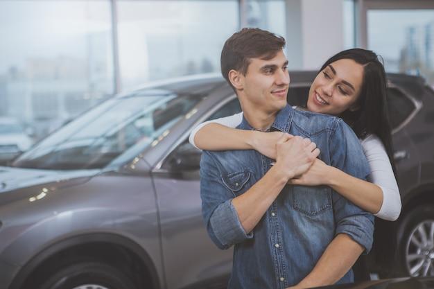 Casal feliz comprando carro novo no salão da concessionária
