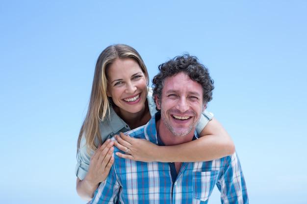 Casal feliz contra o céu azul claro