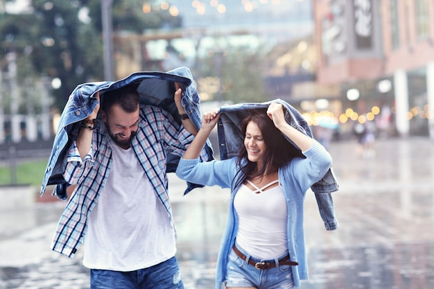 Casal feliz correndo na chuva na cidade