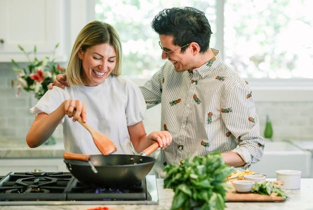 Casal feliz cozinhando na cozinha