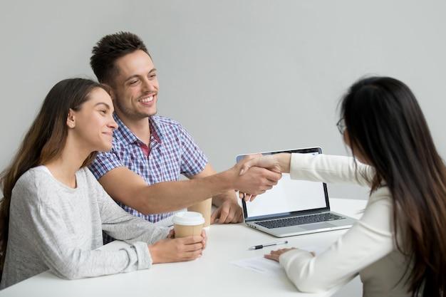 Casal feliz cumprimentando consultor financeiro