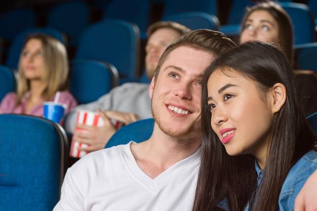 Casal feliz curtindo filmes juntos no cinema local