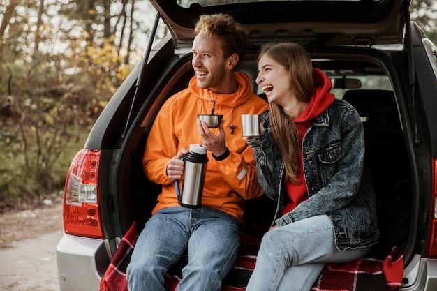Casal feliz curtindo uma bebida quente no porta-malas do carro