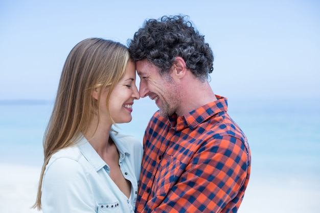 Casal feliz dançando cara a cara na beira-mar