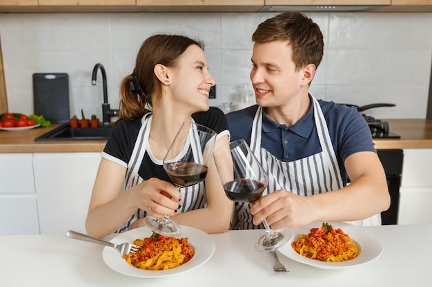 Casal feliz de avental comendo macarrão à bolonhesa com vinho na cozinha moderna. jantar romântico em casa