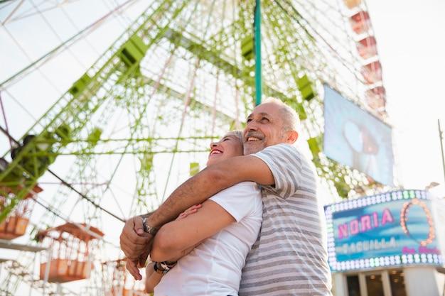 Casal feliz de baixo ângulo abraçando perto da roda gigante