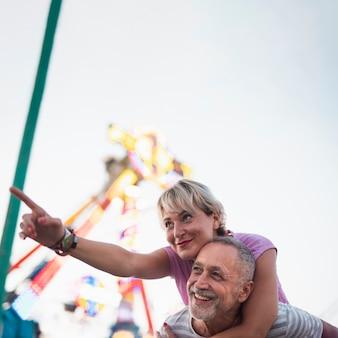 Casal feliz de baixo ângulo no parque de diversões