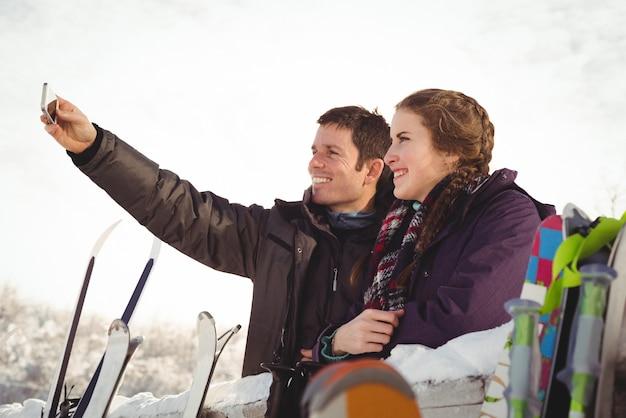 Casal feliz de esquiadores clicando em uma selfie