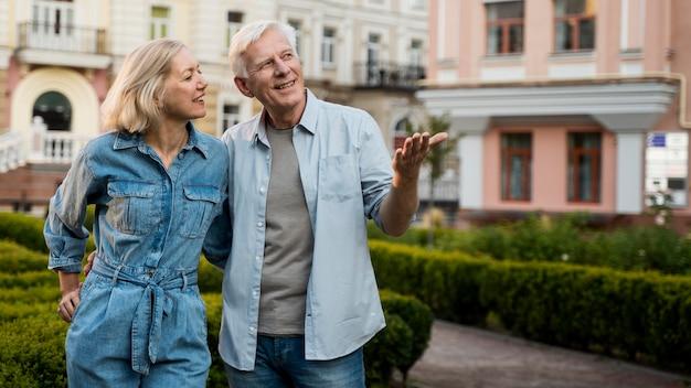 Casal feliz de idosos abraçado, aproveitando o tempo na cidade