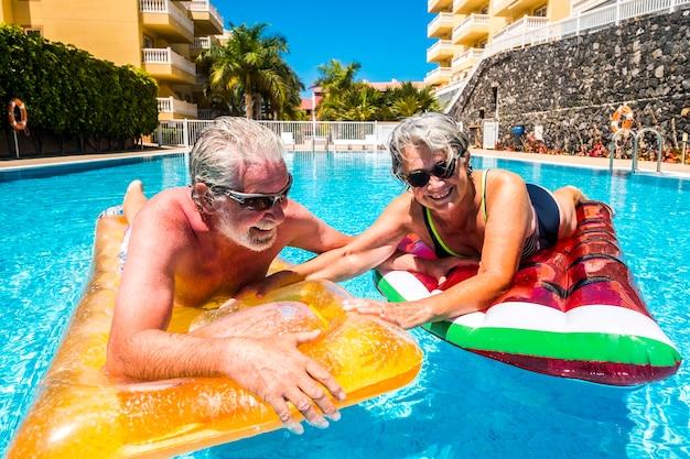 Casal feliz de idosos aproveitando o verão e se divertindo com lilos coloridos juntos na piscina de natação