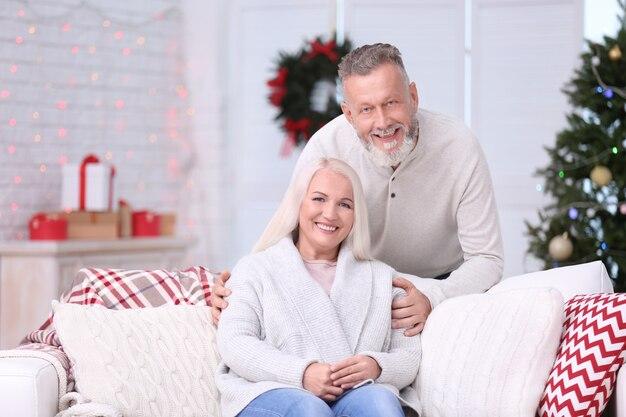 Casal feliz de idosos descansando em casa na véspera de natal