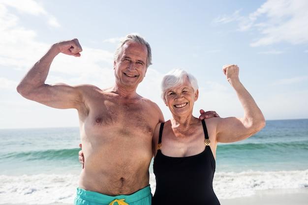 Casal feliz de idosos flexionando seus músculos