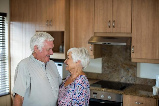 Casal feliz de idosos olhando um para o outro na cozinha de casa