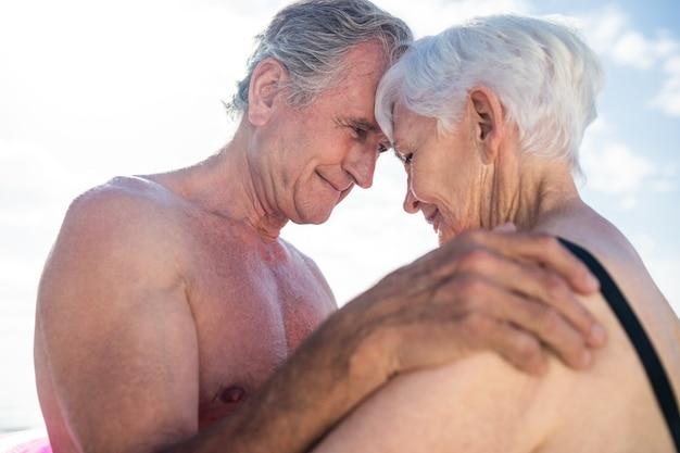 Casal feliz de idosos se abraçando cara a cara na praia